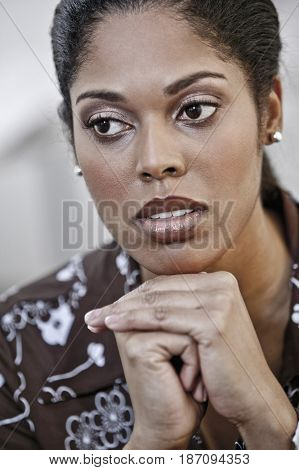 Serious woman with hands on chin