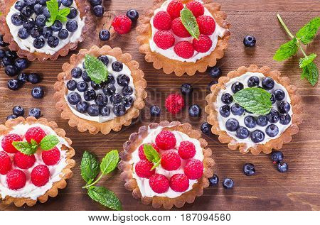 Homemade Sweet Tarts With Berries  On Wooden Table.