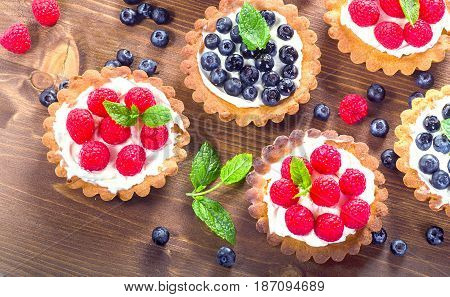 Sweet Tarts With Berries  On A Wooden Table.