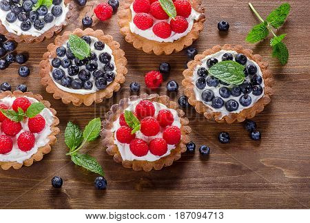 Sweet Tarts With Berries On Wooden Table.