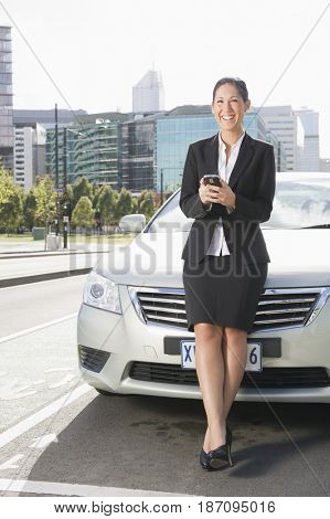 Hispanic businesswoman leaning on car text messaging on cell phone