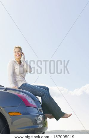 Hispanic woman sitting on car talking on cell phone