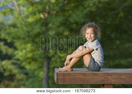 Hispanic girl sitting on pier