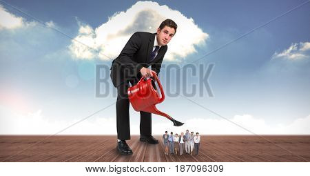 Digital composite of Businessman watering employees on field against sky