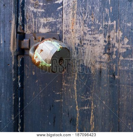 Old rusty padlock on dark blue wooden door. Painted wood texture with industrial object. Retro background with vertical structure and metal elements. With empty space for text.