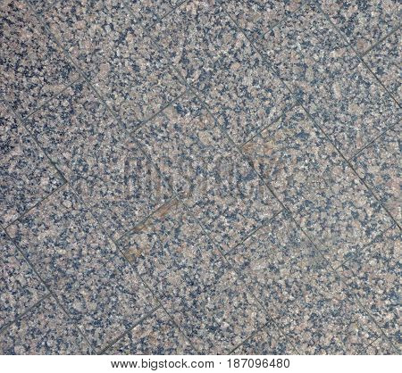 Sidewalk tile texture, lot of randomly placed dark and light dots. Irregular structure, abstract background with place for text. Construction material surface.