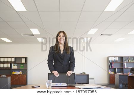 Hispanic businesswoman standing in office