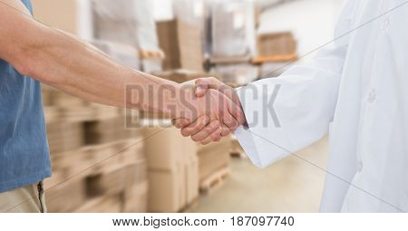 Digital composite of Midsection of man and doctor shaking hands in warehouse