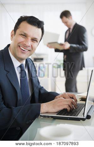 Smiling mixed race businessman using laptop
