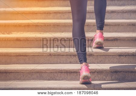 Close up of female legs with sneakers running up the stairs. Sport fitness jogging workout and healthy lifestyle concepts.