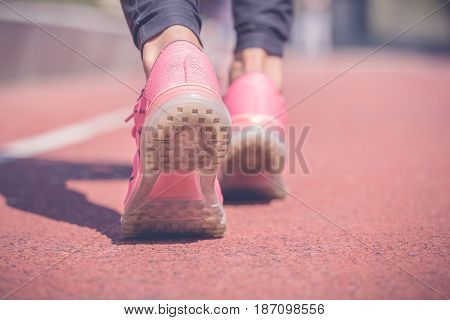 Back side view close up shot of female feet with sneakers on the red running track. Jogging training fitness and healthy lifestyle concepts.
