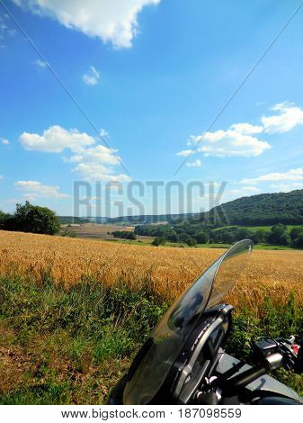 Field with golden corn under blue sky and motorcycle