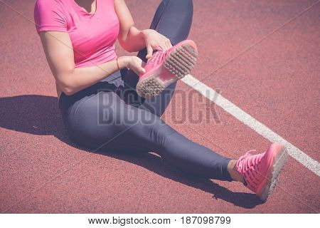 Female jogger hands on foot. She is feeling pain as her ankle or foot is broken or twisted. Accident on running track during the morning exercise. Sport accident and foot sprain concepts.