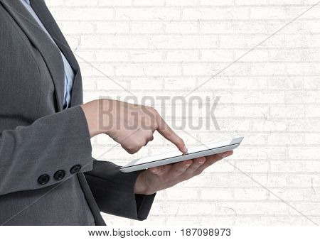 Digital composite of Man touching tablet with white brick wall