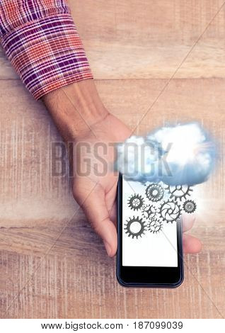 Digital composite of Overhead of hand with phone showing cloud and cog graphics with flare