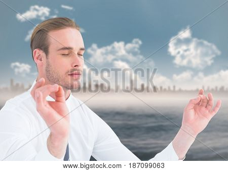 Digital composite of Business man meditating against water and skyline