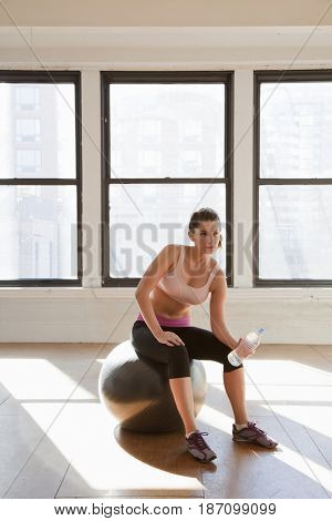 Caucasian woman drinking water after exercise