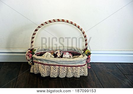 Festive basket with patties on the floor near the wall