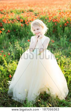 girl model, poppies, wedding, fashion children, nature and summer concept - elegant sweetheart girl bridesmaid with white hair flirts, plays in a field of poppies, she in a white wedding dress