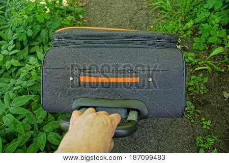 The hand pulls the handle of a large suitcase on the road