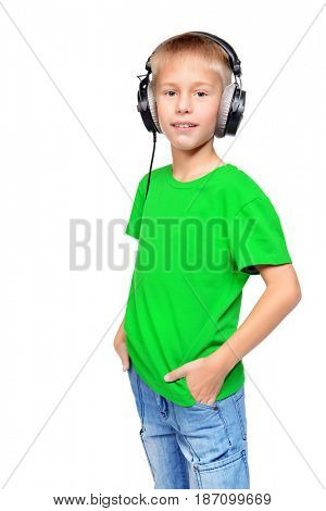 Cool nine year old boy enjoys the music in headphones. Copy space. Isolated over white.