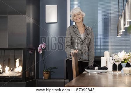 Caucasian woman standing by elegant dining room table