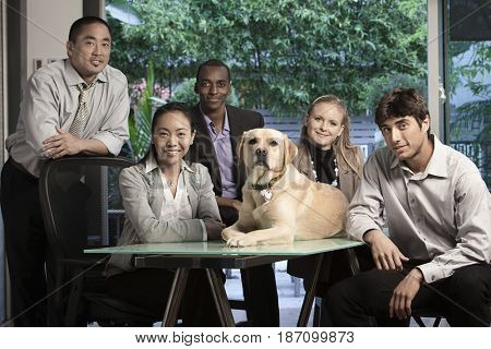 Business people sitting in conference with dog