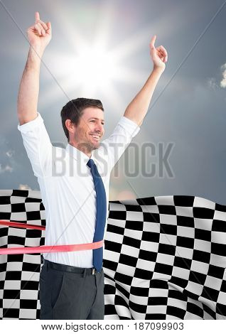 Digital composite of Business man cheering at finish line against sky and sun and checkered flag