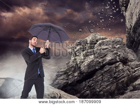 Digital composite of Business man standing with umbrella and mist against falling rocks