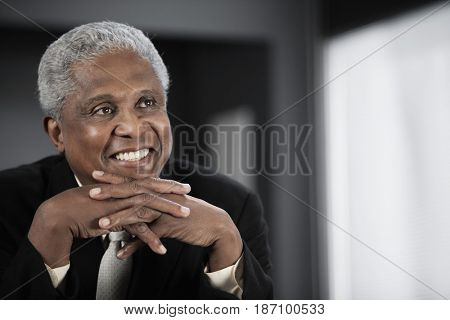 Smiling Black businessman with hands clasped