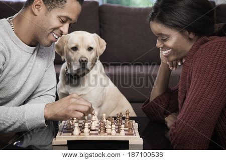Couple playing chess in living room with dog watching