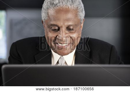 Smiling Black businessman using laptop