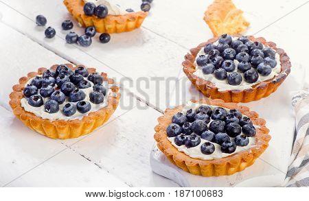 Sweet Blueberry Tarts On White Wooden Board
