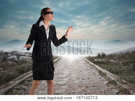 Digital composite of Business woman blindfolded walking down road