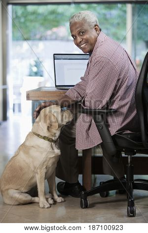 Black man using laptop while dog watches