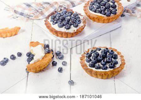 Sweet Blueberry Tarts On  White Wooden Background
