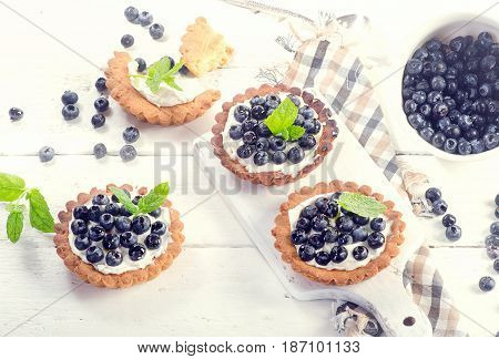 Blueberry Tarts On A White Wooden Table.