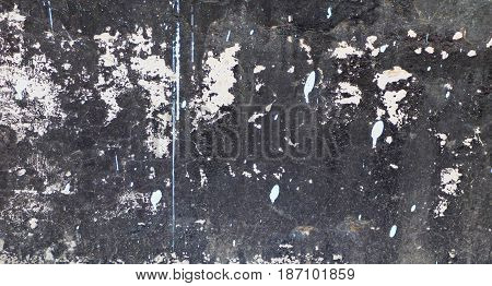Dirty black wall texture with cracks and white spots. Abstract grunge background with random structure and place for text.