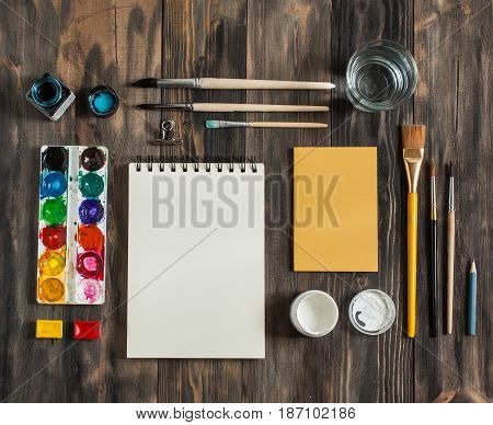 Mock Up. Creative Space. Artistic Work Tools On Dark Wooden Table: Watercolor, Paintbrushes And Wate