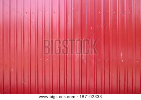 Goffered metal texture, corrugated red steel background. Industrial metallic surface. Closeup view.