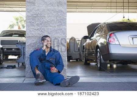 Hispanic worker taking a break and talking on cell phone