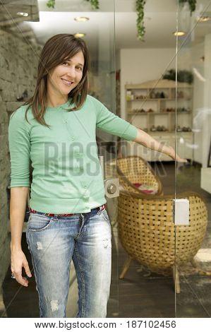 Hispanic woman standing in shop doorway