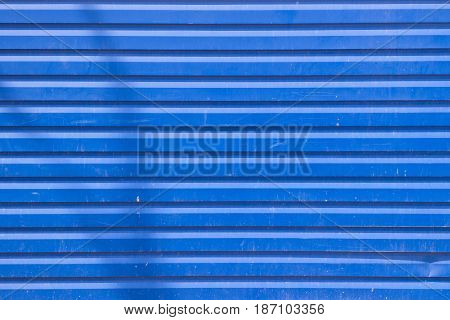 Bright blue metal siding wall texture with some cracks
