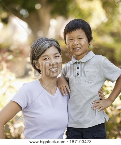 Asian mother and son hugging outdoors