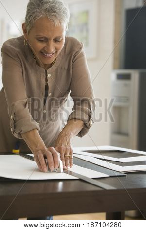 Mixed race woman cutting picture mat