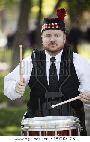 Man in Scottish clothing playing drums