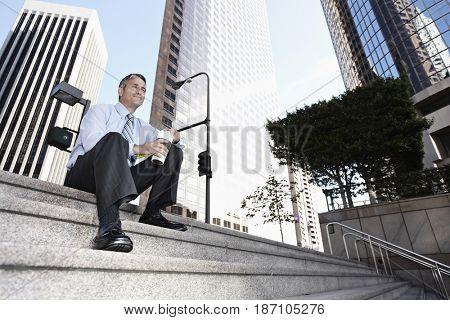 Hispanic businessman sitting on steps drinking coffee