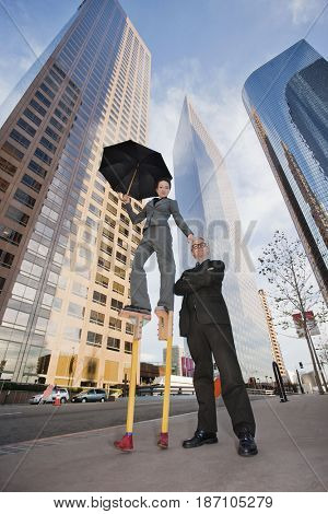 Caucasian businesswoman on stilts in urban environment standing with co-worker
