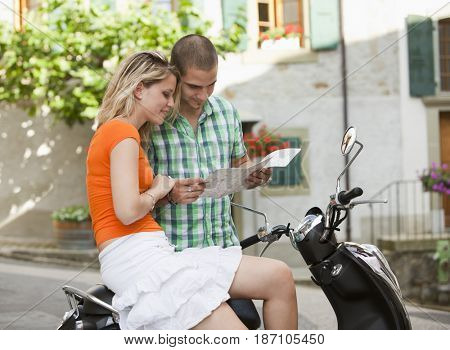 Couple with scooter looking at map