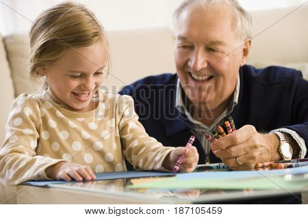Caucasian grandfather watching granddaughter coloring